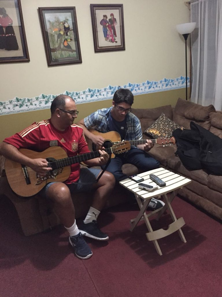Spanish immersion participant playing guitar with his host dad!